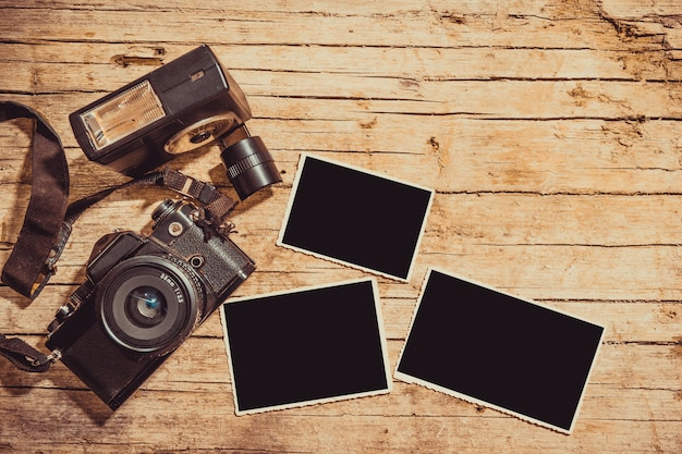 Cámara de película vintage y dos marcos de fotos en blanco en mesa de madera