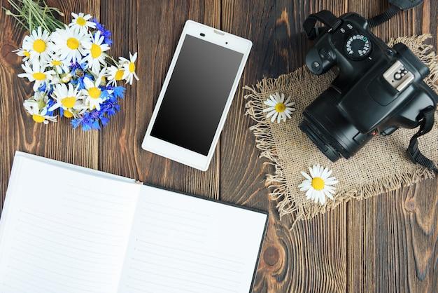 Cámara, portátil, teléfono móvil y flores de campo sobre fondo de madera oscura. lanza libre. ganancias en la foto.