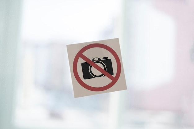 Una cámara prohibida la etiqueta engomada del icono del símbolo en la pared en el área de restricción de tiro en un lugar público