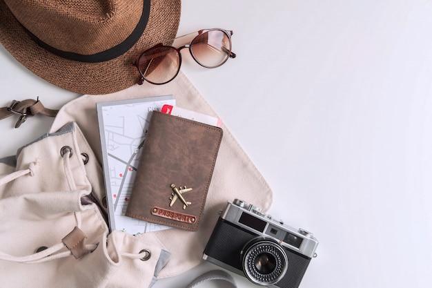 Cámara retro con accesorios de viaje y artículos sobre fondo blanco