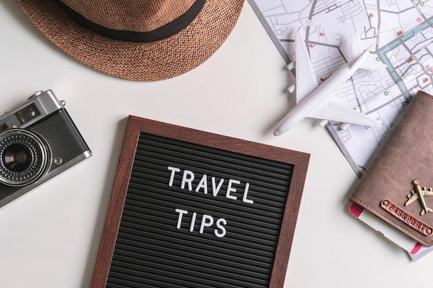Cámara retro con avión de juguete, mapa y pasaporte sobre fondo blanco