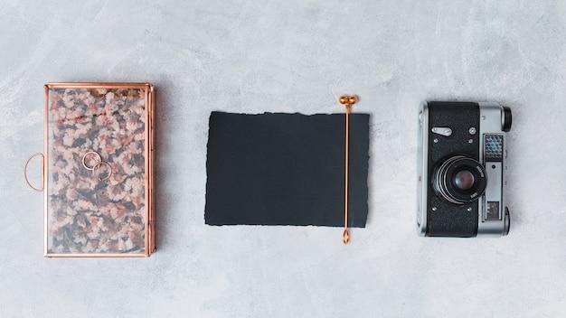 Cámara retro cerca de papel oscuro y caja creativa.
