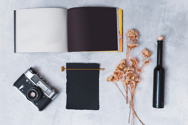 Cámara retro cerca de papel oscuro, ramitas de planta seca, cuaderno y botella.
