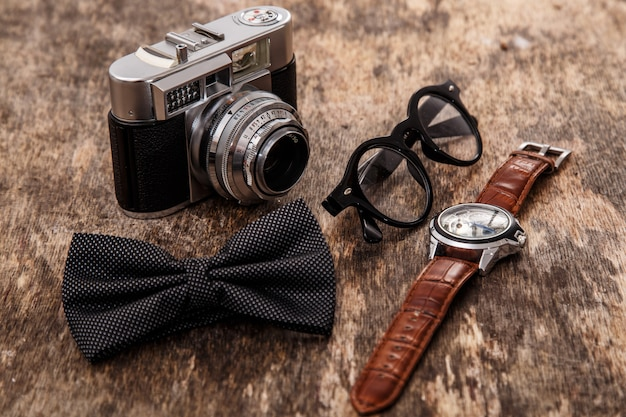 Cámara retro, reloj, corbatín y gafas