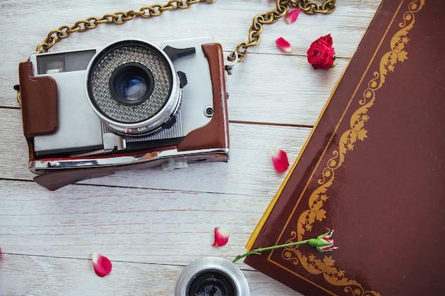 Cámara retro rollo de película fotográfica y flores en madera blanca