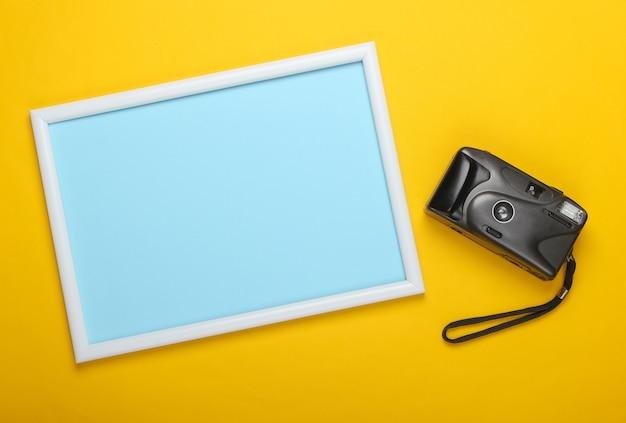 Cámara retro en superficie amarilla con marco de fotos