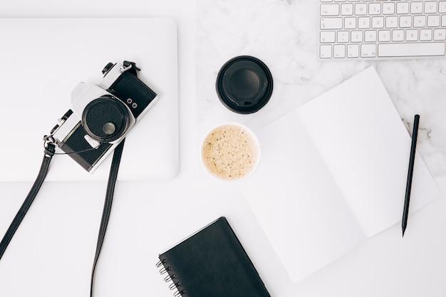 Cámara retro en tableta digital; taza de café; papel; lápiz; diario y teclado en mesa blanca