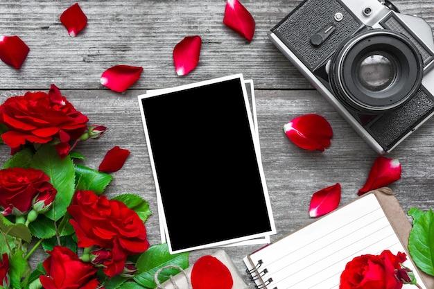 Cámara retro vintage y marco de fotos en blanco con ramo de flores rosas rojas y cuaderno forrado