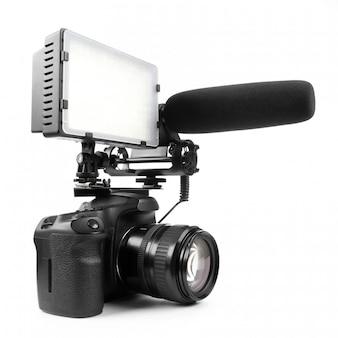 Cámara de video dslr aislada en la superficie blanca con micrófono y luz.