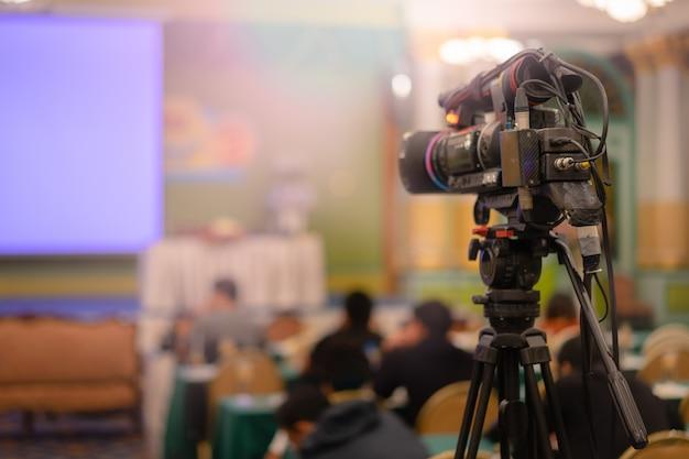Cámara de video tomando video en vivo con gente trabajando.