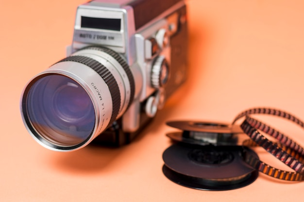 Cámara de videocámara vintage con tira de película sobre fondo color melocotón