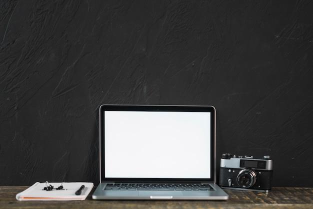 Cámara vieja retra y computadora portátil de la pantalla en blanco con efectos de escritorio en la tabla de madera