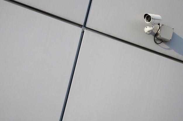 Cámara de vigilancia blanca incorporada en la pared metálica del edificio de oficinas.