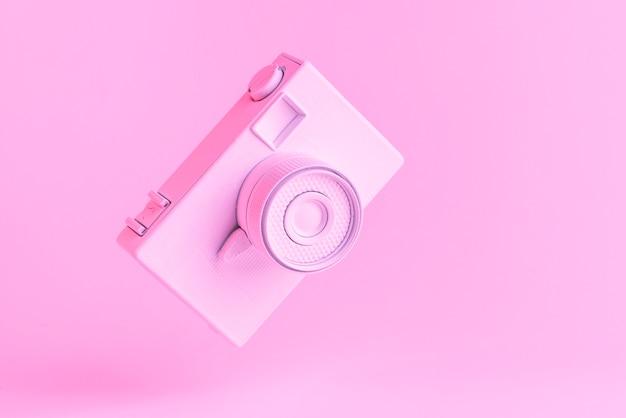 Cámara vintage inclinable contra fondo rosa