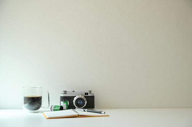 Cámara vintage y película con café en la mesa