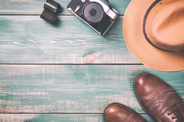 Cámara vintage con película, zapatos marrones y sombrero fedora sobre fondo de madera verde.