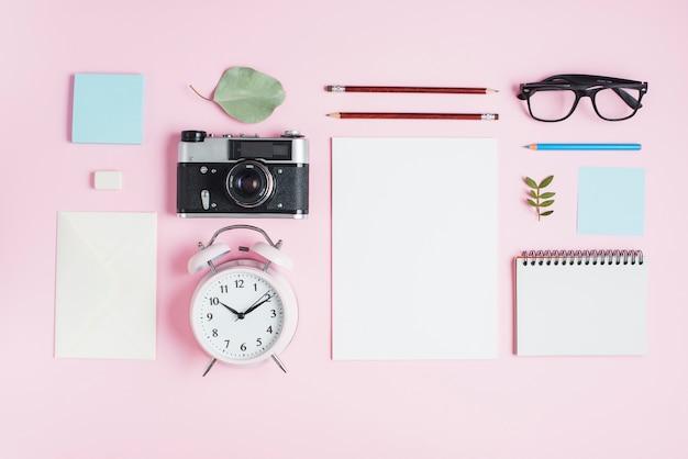 Camara vintage reloj despertador y papelería sobre fondo rosa.