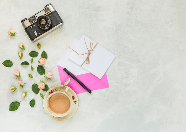 Camara vintage rosa rosada; hojas verdes; sobre; papel; taza de café y pluma sobre fondo concreto
