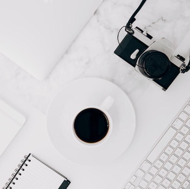 Camara vintage teclado; taza de café y diario sobre fondo de mármol blanco
