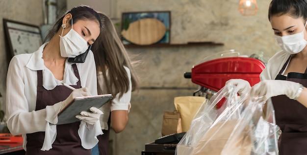 La camarera asiática panorámica toma pedidos desde el teléfono móvil para llevar o recoger pedidos en la acera.