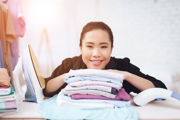 Camarera asiática sonriente con ropa doblada.