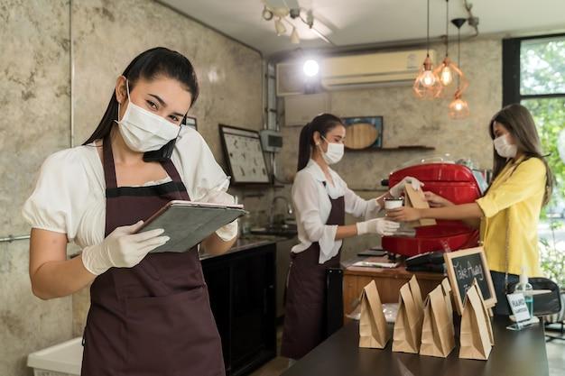 La camarera asiática toma el pedido desde el teléfono móvil para llevar y recoger pedidos en la acera.