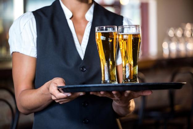 Camarera con bandeja de servir con dos vasos de cerveza