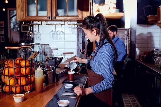 La camarera barista hace leche caliente en el bar de la cafetería.