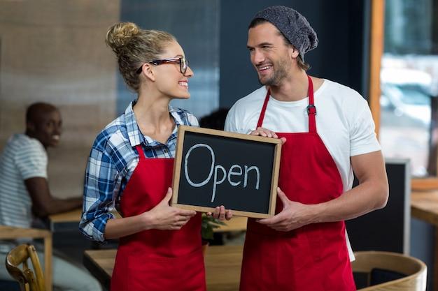 Camarera y camarero de pie con letrero abierto en café