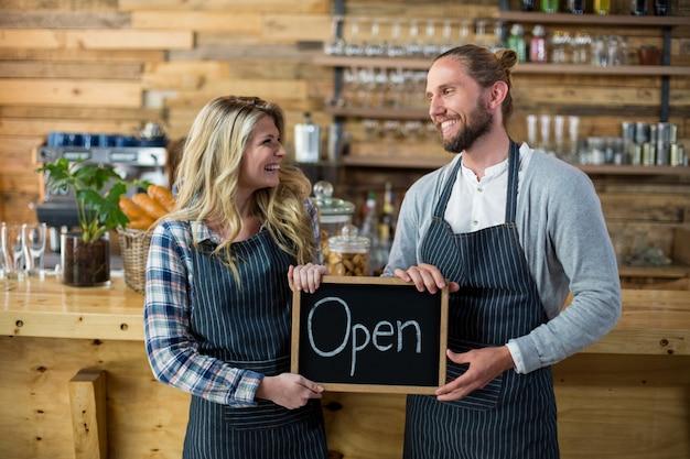 Camarera y camarero de pie con letrero abierto en cafe