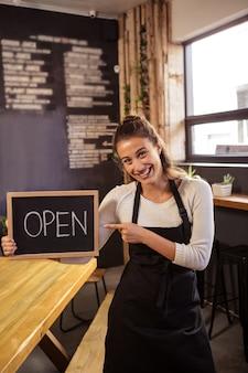 Camarera con un cartel con abierto