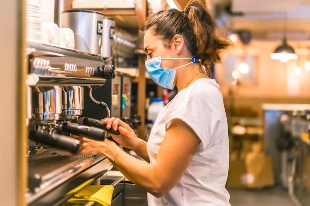 Una camarera caucásica de pelo oscuro con mascarilla en un bar. preparando un café con leche con la máquina