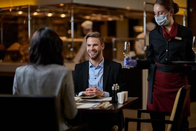 Camarera competente sosteniendo un vaso con una bebida en la mano izquierda y colocándolo sobre la mesa entre dos personas