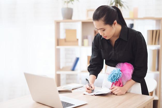 La camarera concentrada escribe el informe en la computadora portátil.
