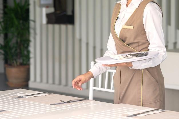 Camarera contra vajilla vacía, ajuste de la tabla. de cerca
