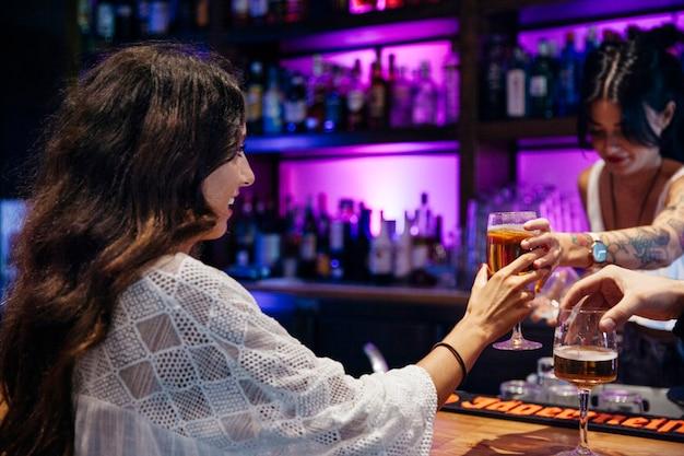 Camarera dando bebida a mujer