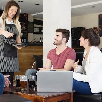 Camarera dando menús a los clientes en el bar