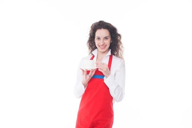 Camarera en delantal rojo ofreciendo una taza de café aislado sobre fondo blanco.