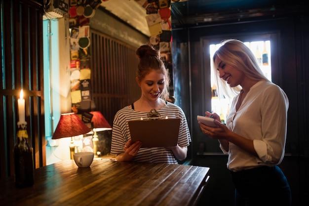 Camarera discutiendo el menú con el cliente.