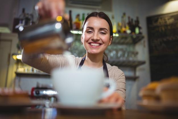 Camarera hacer taza de café en el contador en el café