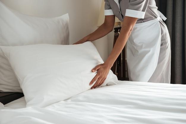 Camarera haciendo cama en habitación de hotel