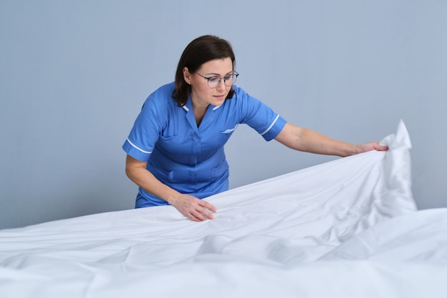 Camarera haciendo cama de invitados en la habitación del hotel. servicio, limpieza, personal, concepto de hotel.