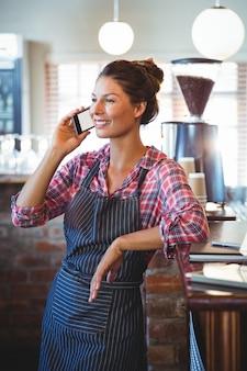 Camarera haciendo una llamada telefónica