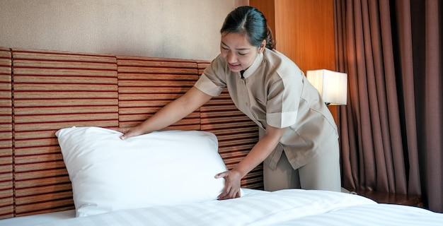 Camarera de hotel haciendo la cama en la habitación de hotel de lujo lista para viajes turísticos.