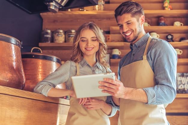 Camarera y joven camarero en delantales están usando una tableta.