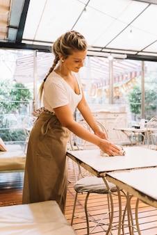 Camarera limpiando mesa