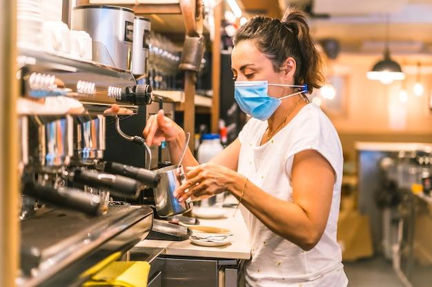 Una camarera con una mascarilla en un bar. hacer un café con leche con la máquina de café una mañana de primavera