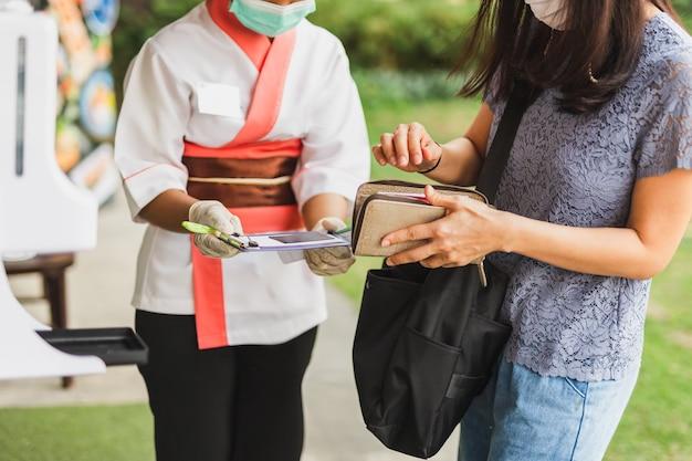 Camarera de la mujer en la máscara médica que recibe la tarjeta de crédito del cliente.