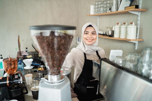 Camarera mujer sosteniendo un molinillo de café