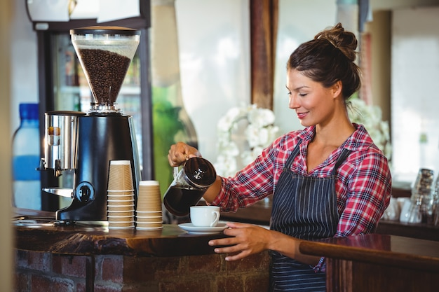 Camarera preparando un café